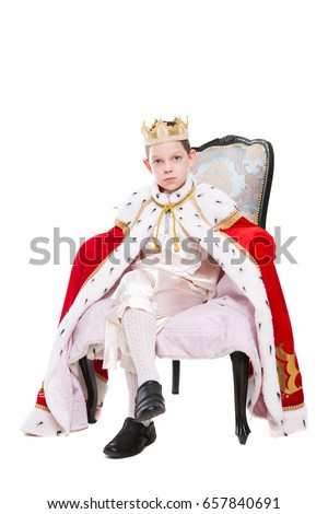 Cute boy wearing costume of a king posing in the throne. Isolated on white