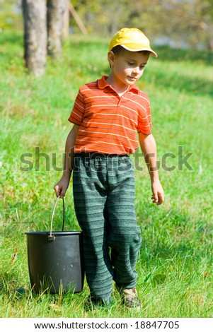 Cute boy with a bucket going to pick up apples in a garden - stock photo