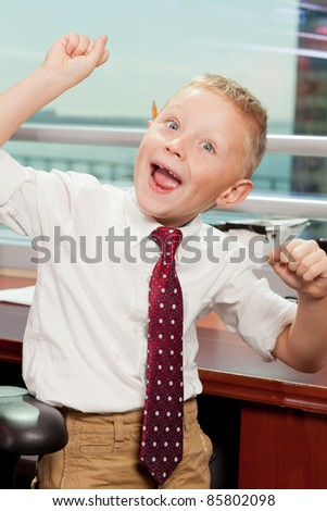 Cute boy with a goofy expression in business attire in a corporate office.