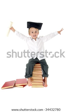 Cute Boy with arms in air waves diploma and wears graduation cap while sitting on stack of books