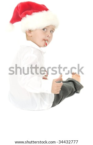 Cute Boy with Santa hat has candy cane in mouth and handful of Candy canes