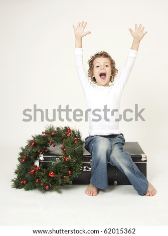 Cute boy with suitcase and christmas decoration waiting for Christmas