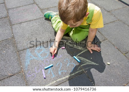 Cute boy write with colored chalks. Little kid draws with chalks. School, ABC and 123 sigh written with colored chalks. Vacation concept. Education concept. School and fun time. Play and game time.