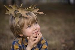 cute boy 4 years old. On head lie brown dry oak leaves. Autumn walks in park in  fresh air. Positive, relaxed, joy. autumn harmony