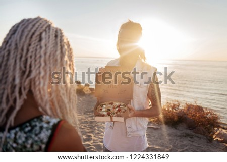 Cute boyfriend. Cute boyfriend opening box with pizza asking his woman to marry him standing near the sea #1224331849