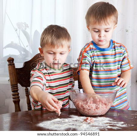 Cute boys are mixing mincemeat in a bowl