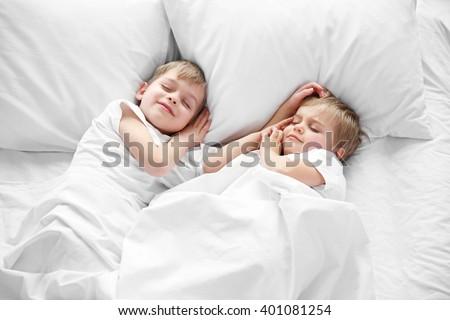 Cute boys sleeping in bed under blanket, closeup