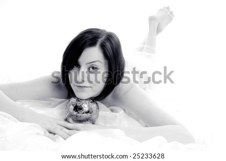 Cute bride resting her head on a silver magic ball, high key isolated on white
