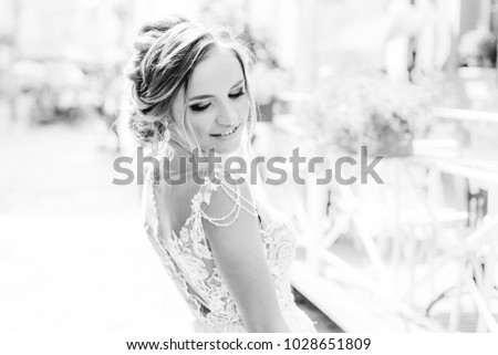 cute bride with a beautiful hairstyle and makeup on black and white photography #1028651809