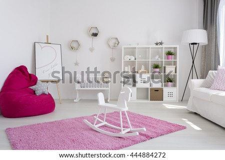 Cute bright baby room for a girl, with a pink fluffy carpet and a wooden rocking horse