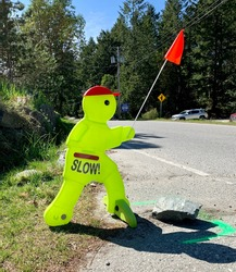 Cute bright colour mascot warning drivers to drive slowly for safety