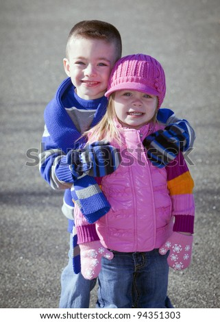 Cute brother and sister in winter hugging outside