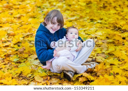 Cute brother holding his baby sister playing between yellow maple leaves