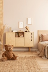 Cute brown teddy bear sitting on the floor of beige bedroom interior with wooden commode