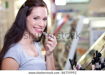 Cute brunette buying cosmetics. Applying lipstick in a drugstore. Shallow DOF.