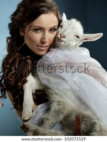 Cute brunette holding a little goat