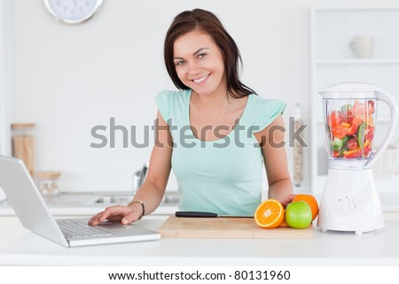 Cute brunette with a laptop and fruits in her kitchen