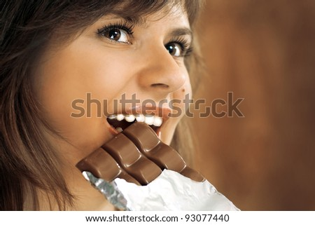cute brunette with brown eyes eats chocolate