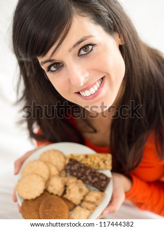 Cute brunette woman eating sweet cereal and chocolate biscuits in bed. Adorable and charming model, looking at camera and smiling.