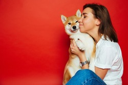Cute brunette woman in white t shirt and jeans holding and embracing Shiba Inu dog, has eyes closed with pleasure, isolated on red background. Love to the animals, pets concept