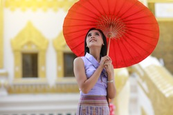 Cute Burmese women with traditional  Burma dress holding red umbrella walk in temple