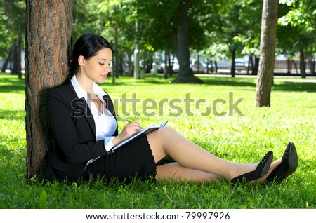 Cute business woman sitting on the grass and making notes, in summer park.