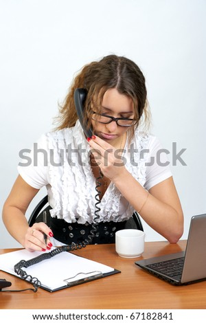 Cute business woman talking phone and writing something in the office