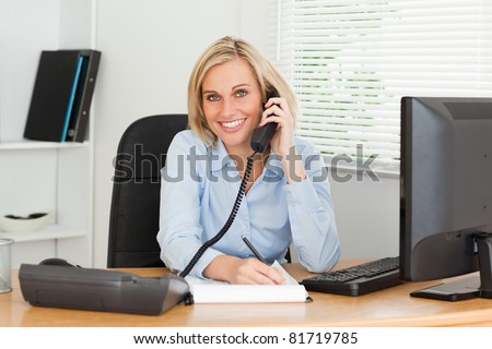 Cute businesswoman on phone writing something down looks into camera in her office