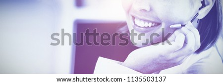 Cute businesswoman talking with clients in front of her computer in the office #1135503137