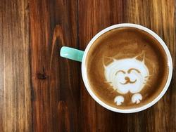 Cute cat face latte art coffee in white cup on wooden table ; love coffee, Cute Neko latte art coffee. animal latte art