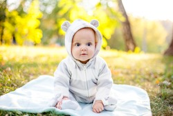 Cute caucasian baby boy in park looks at camera