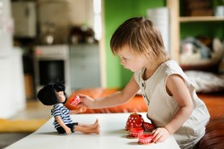 Cute caucasian baby toddler playing with a doll and toy utensils on table. kid takes care of the doll, the child pours tea coffee from  teapot, treats the doll with tea. role-playing game