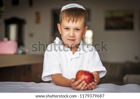 Cute Caucasian blue-eyed boy in a traditional Jewish white kippah cap with an apple in his hands. Russian Jewish boy celebrating Jewish New Year - Rosh Hashanah.