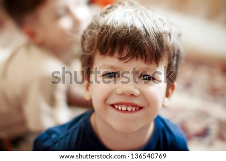 Cute caucasian boy with teeth smile, brother background