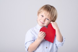 Cute Caucasian child is tenderly holding toy red heart on white background. Eye contact. Studio light. Concept of childhood, love, mother's day, health care, valentine. Horizontal. Copy space.
