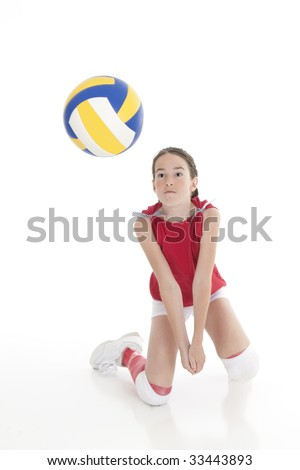 Cute Caucasian girl hitting the ball in volleyball isolated on a white background