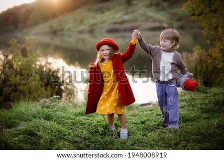 Cute Caucasian girl in a red coat and a hat with a boy dancing with doll baby and stroller in the park, children like parents with child hugging, game concept and parenthood, family values Stock photo ©