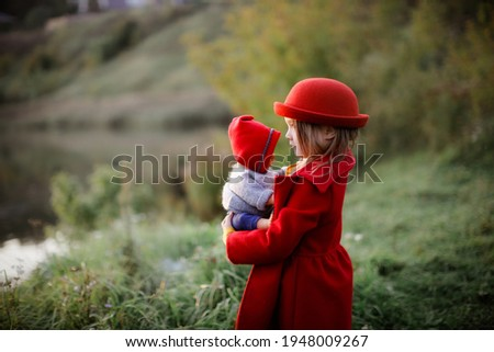 Cute caucasian girl in a red coat and hat with a doll baby in the park, baby like a mom, a girl playing with a doll, taking care of a doll, play and motherhood concept, little lady, autumn park Stock photo ©
