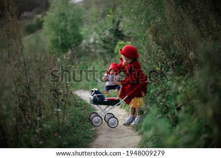 Cute caucasian girl in a red coat and hat with baby doll and doll stroller in the park, a child like mom, girl playing with doll, taking care of doll, role play and motherhood concept, little lady Stock photo ©