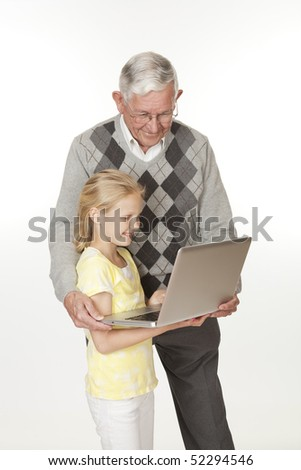 Cute Caucasian granddaughter showing her grandfather something on the computer