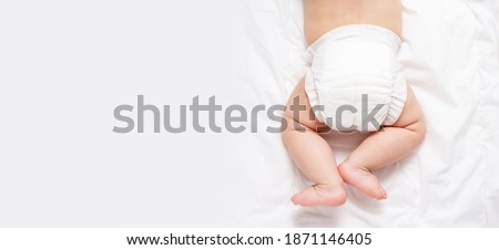 Cute caucasian infant baby in white nappy on light grey blanket. Top view. Banner format. Copy space. Diaper change and care of baby's skin.