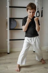 cute caucasian karate boy standing in stance in white kimono pants and black tee shirt at home near wall bars. Individual martial art sport for kids.