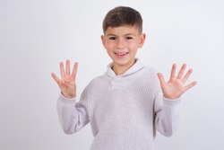 Cute Caucasian kid boy wearing knitted sweater against white wall showing and pointing up with fingers number nine while smiling confident and happy.