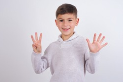Cute Caucasian kid boy wearing knitted sweater against white wall showing and pointing up with fingers number eight while smiling confident and happy.