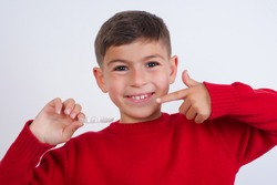 Cute Caucasian kid boy wearing red knitted sweater against white wall holding invisible braces aligner smiling and pointing to his teeth. Dental healthcare concept.