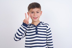 Cute Caucasian kid boy wearing stripped knitted sweater against white wall showing and pointing up with fingers number two while smiling confident and happy.