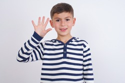 Cute Caucasian kid boy wearing stripped knitted sweater against white wall showing and pointing up with fingers number five while smiling confident and happy.