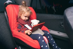 Cute caucasian little child sitting at safety car seat for children, fastened by safety belts, watching cartoons and videos at digital device, evening time, holding bear toy, funny facial expression.