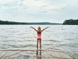 Cute Caucasian little preschool blonde girl in pink swimsuit standing on wooden lake river dock with her hands above. Concept of harmony with nature, happy healthy active childhood. View from back.