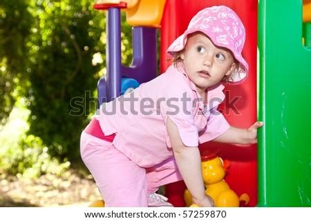Cute caucasian toddler girl having fun playing on playground.